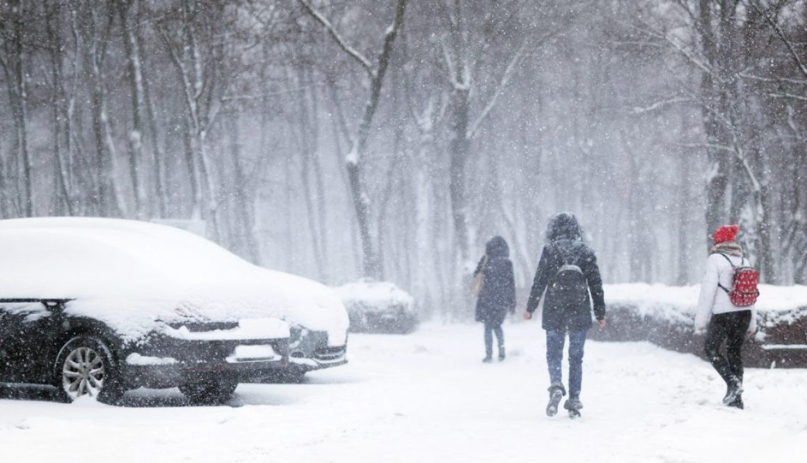 People Walking Through City Street Covered With Snow During Heav